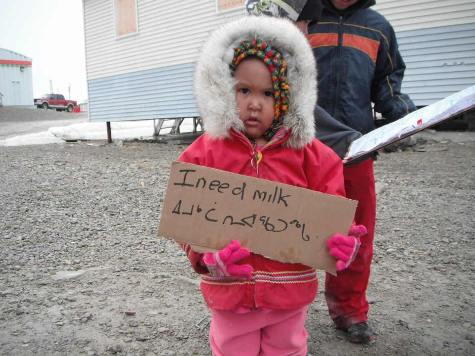 "Child holding sign that says, ""I need milk"" in Northern indigenous language and English"
