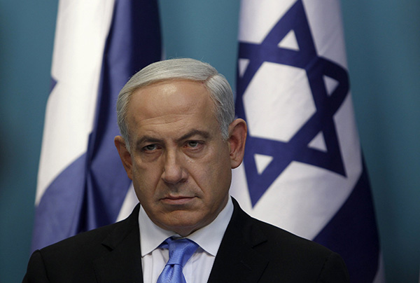 Netanyahu stands before the flag of Israel