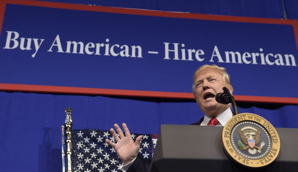 """Donald Trump at the podium in front of a """"Buy America"""" banner"""
